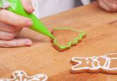 Decorating gingerbread cookies (Christmas tree) with green icing — Stock Photo