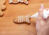 Decorating gingerbread cookies (fish) with white icing, selectiv — Stock Photo