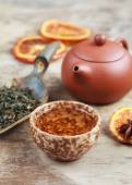 Cup of herbal tea, earthenware teapot and candied orange on the  — Stock Photo