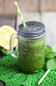 Healthy green smoothie made from spinach, kiwi, bananas and oranges in a jar with red straw on a wooden table, selective focus — Stock Photo