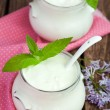 Homemade yogurt in two small glass jars on a wooden table with p — Stock Photo #75569911