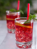 Cocktail with lemon slices and ice cubes in a glass — Stock Photo