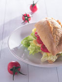 Bread roll books with cheese, salad sheets and tomatoes — Stock Photo