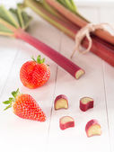 Freshly rhubarb with strawberries on a tray — Stock Photo