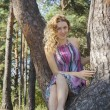 Bright sunny day in autumn forest girl sitting on a pine tree. — Stock Photo #53520813