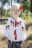 The little blue-eyed blonde standing in embroidery in the woods — Stock Photo