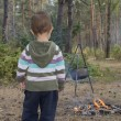 The child in the forest stands near the fire where the food is c — Stock Photo #54006173