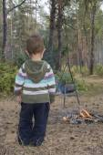 The child in the forest stands near the fire where the food is c — Stock Photo