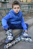 Sad little boy sits shod rollers on the curb. — Stock Photo