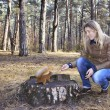 In the woods near the stump girl feeds a squirrel with nuts. — Stock Photo #56616595