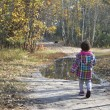 Little girl in autumn forest is on the road near the puddle. — Stock Photo #57270567