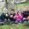 Kids on spring meadow sit on the grass and eat cookies. — Stock Photo #62559875