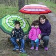 Mom with son and daughter sitting in the woods under umbrellas. — Stock Photo #63479263