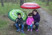 Mom with son and daughter sitting in the woods under umbrellas. — Stock Photo