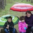 Mom with son and daughter sitting in the woods under umbrellas. — Stock Photo #63481885