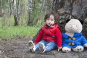 Spring in the forest little girl playing with a toy bear. — Stock Photo