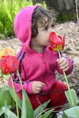 Little girl smelling a spring tulip. — 图库照片