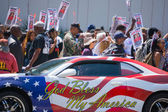 Car painted with american flag colors in front of protestors — Stock Photo