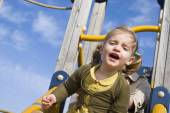 Young girl on slide in playground — Stock Photo