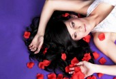 Beautiful long haired girl laying in petals of red roses on viol — Stock Photo