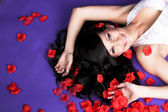 Beautiful long haired girl laying in petals of red roses on viol — Photo