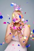 Portrait of beautiful woman blowing confetti in the air, party n — Stock Photo