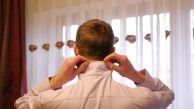 Man (the groom) raises collar shirt — Stockvideo