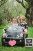 Little newlyweds in a small toy car — Stockfoto