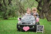 Little newlyweds in a small toy car — Foto Stock