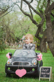 Little groom in a toy car — Stock Photo