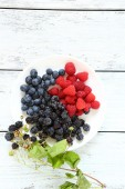 Raspberries and blackberries on a white plate — Stock Photo