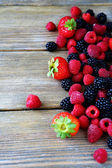 Raspberries and blackberries on the boards — Stock Photo