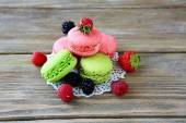 Green and pink macaroon with berries — Stock Photo
