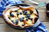 Pie with plums in baking dish — Stock Photo