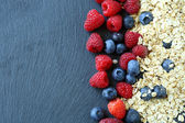 Healthy breakfast and berries on slate background — Stock Photo