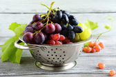 Different varieties of grapes in colander — Stock Photo