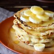 Sweet pancakes with honey and bananas on a plate — Stock Photo #54032601