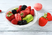 Strawberries raspberries and blueberries with macaroon — Stock Photo