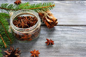 Aromatic anise in jar with pine branches on the boards — Stock Photo