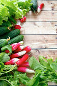 Fresh radishes and other vegetables on wooden boards — Stock Photo
