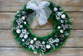 Christmas wreath with a bow on the boards — Stock Photo