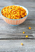 Seabuckthorn in a bowl on boards — Stock Photo