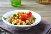 Delicious salad with boiled chickpeas and tomatoes on a bowl — Stockfoto