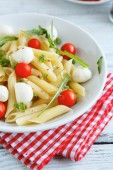 Penne on a white plate with tomatoes and mozzarella cheese — Stock Photo