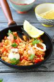 Paella with prawns, mussels and Lemon in a frying pan — Stock Photo