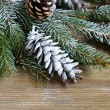 Christmas fir branch covered with artificial snow on boards — Stock Photo #55033865