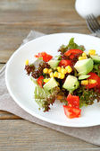 Summer salad with avocado, tomatoes and corn on a white plate — Stock Photo