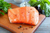 Red fish fillet with greens on a cutting board — Stock Photo