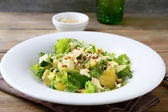Fresh salad with avocado, orange and crushed nuts on a white pla — Stock Photo