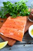 Salmon with greens and lemon on a board — Foto de Stock